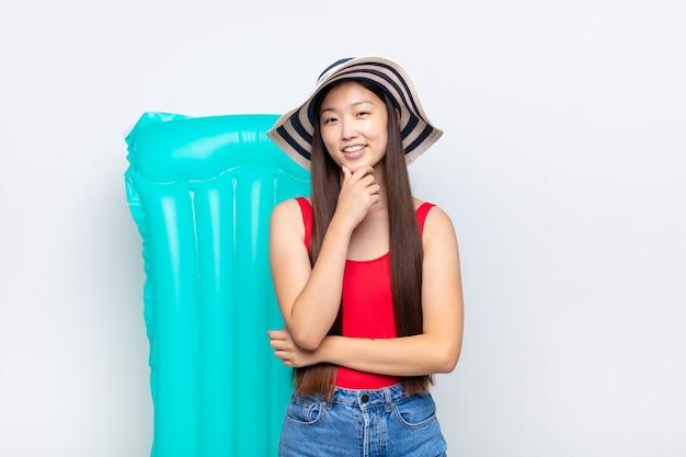 Азиатская молодая женщина улыбается, наслаждается жизнью, чувствуя себя счастливой