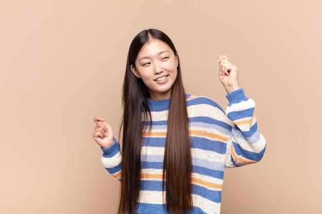 Азиатская молодая женщина улыбается, чувствует себя беззаботной, расслабленной и счастливой