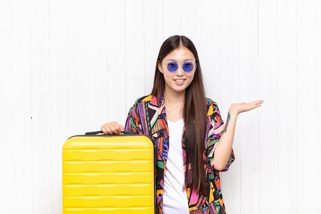 Азиатская молодая женщина улыбается, чувствует себя уверенно, успешной и счастливой