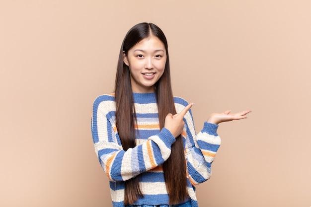 笑顔、幸せ、のんきと満足を感じて、側面のコピースペースのコンセプトやアイデアを指しているアジアの若い女性