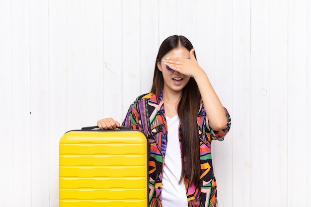 Asian young woman smiling and feeling happy, covering eyes with both hands and waiting for unbelievable surprise.