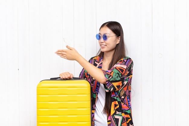笑顔、あなたに挨拶し、成功した取引、協力の概念を閉じるために握手を提供するアジアの若い女性