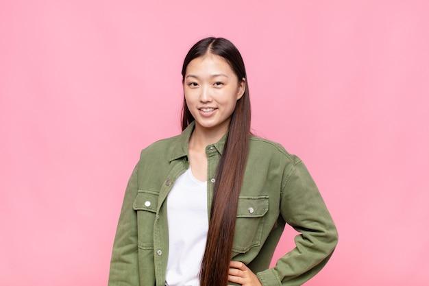 ヒップと自信を持って、前向きで、誇りに思って、フレンドリーな態度で幸せに笑っているアジアの若い女性