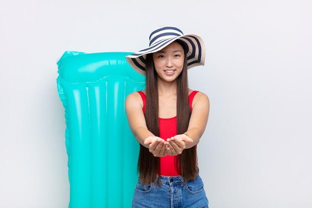 フレンドリーで自信に満ちた前向きな表情で幸せそうに笑っているアジアの若い女性は、オブジェクトやコンセプトを提供し、示しています。夏のコンセプト