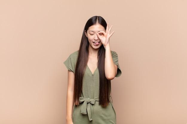 Азиатская молодая женщина счастливо улыбается с забавным лицом, шутит и смотрит в глазок
