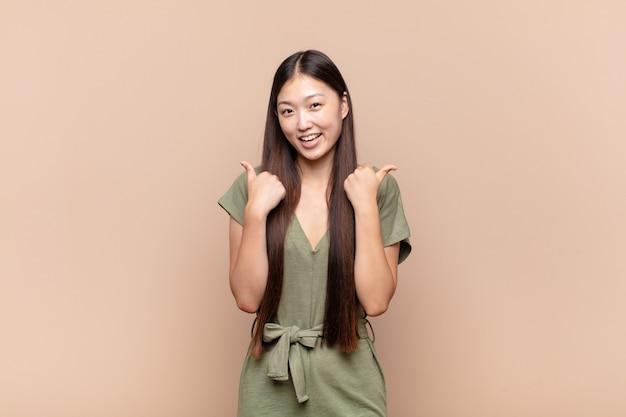 嬉しそうに笑って幸せそうに見えるアジアの若い女性、のんきな孤立感