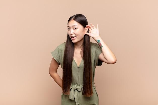 笑顔、不思議なことに横を向いているアジアの若い女性