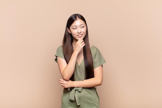 Азиатская молодая женщина улыбается со счастливым, уверенным выражением лица, положив руку на подбородок