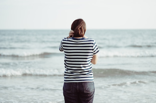Asian young woman standing facing the sea. feeling really lonely,