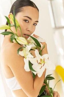 아름다운 꽃다발을 들고 서 있는 아시아 젊은 여성