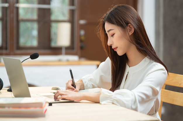 Asian young woman student writing on notebook look at laptop screen and learning online courses