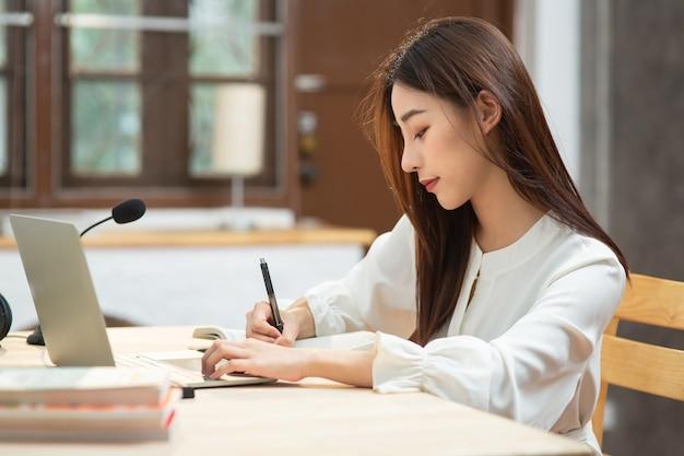 노트북에 글을 쓰는 아시아 젊은 여성 학생은 노트북 화면을 보고 온라인 과정을 학습합니다.