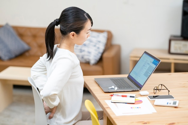 Asian young woman suffering from back pain at work