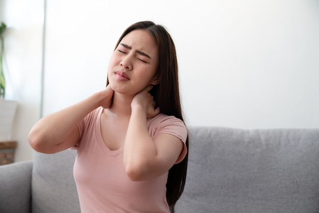 Asian young woman suffering neck pain sitting on sofa couch after finished work at home