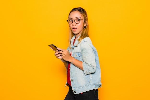 Азиатская молодая женщина удивила и держащ смартфон на желтой стене