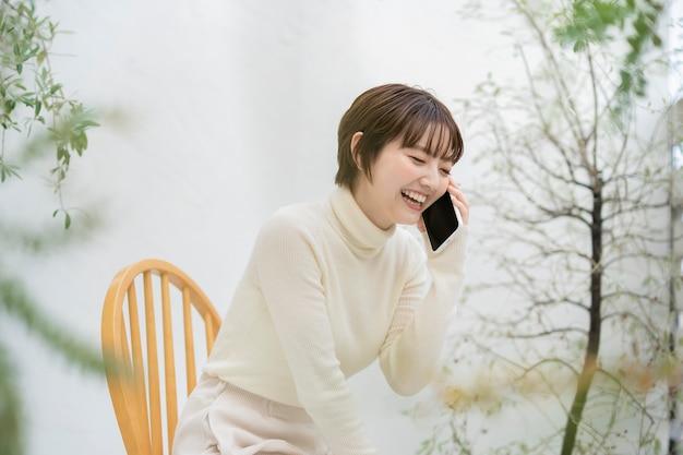 Азиатская молодая женщина разговаривает по смартфону с улыбкой на открытом воздухе