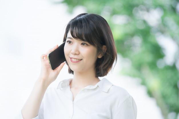耳にスマートフォンで誰かと話しているアジアの若い女性