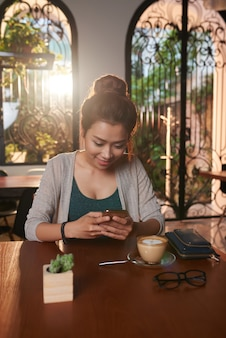 Asian young woman texting in cafe