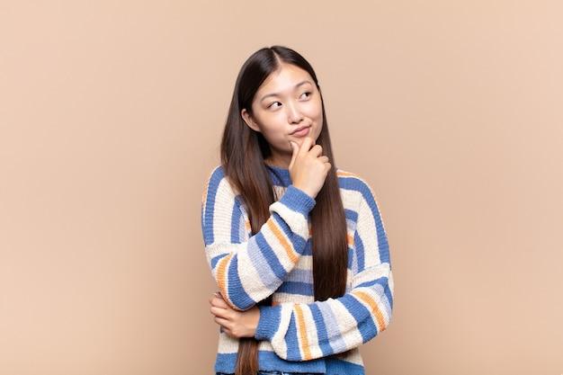 Азиатская молодая женщина думает, чувствует себя сомнительно и смущенно, с разными вариантами, задаваясь вопросом, какое решение принять