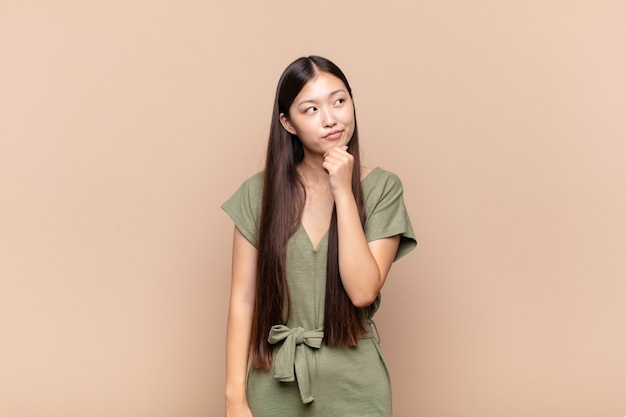 Asian young woman thinking, feeling doubtful and confused, with different options, wondering which decision to make