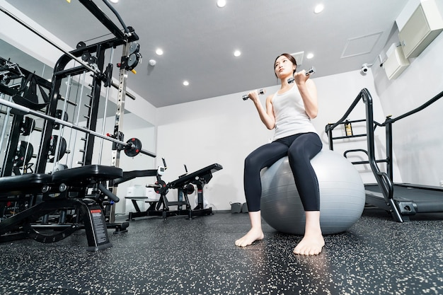 Азиатская молодая женщина тренируется с балансировочными мячами и гантелями