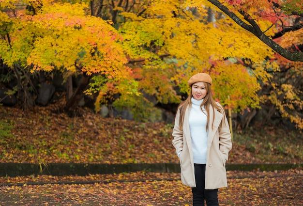 Азиатская молодая женщина путешествует в японии осенний сезон