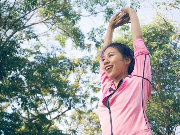アジアの若い女性は、朝の運動の前にストレッチ体をウォームアップ