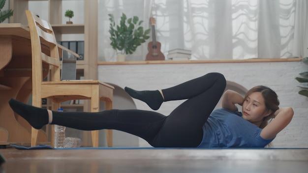 집에서 거실에서 운동하기 위해 노트북을 사용하여 온라인 학습을 보고 있는 아시아 젊은 여성