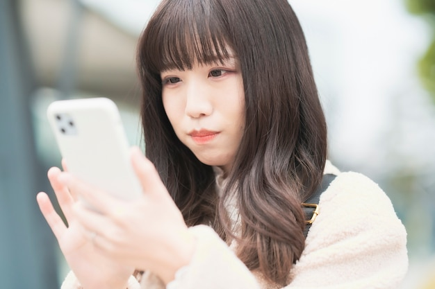 Asian young woman watching the screen and operating a smartphone