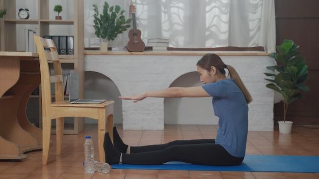 집에서 거실에서 운동하기 위해 노트북을 사용하여 온라인 학습 튜토리얼을 보고 있는 아시아 젊은 여성