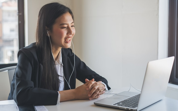 Asian young woman wear earphones talking in video conference