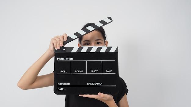 아시아 젊은 여성은 얼굴 마스크를 쓰고 손을 잡고 있는 클래퍼 보드나 영화 슬레이트는 흰색 배경에 그녀의 얼굴을 가렸습니다.