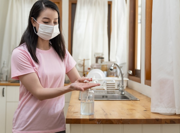 コロナウイルスまたはcovid19の発生時に、自宅で作業し、消毒ジェルで手を掃除するフェイスマスクまたは保護マスクを着用したアジアの若い女性。