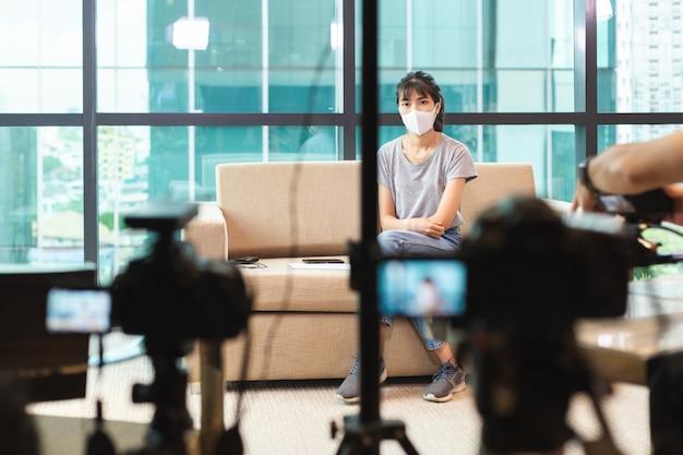 Предохранение от лицевой маски азиатской молодой женщины нося и сидеть на софе