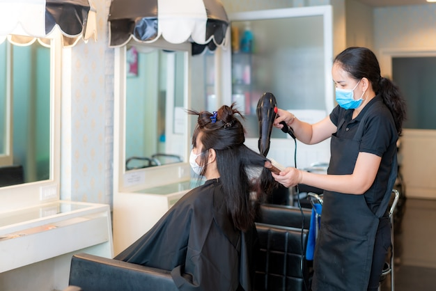 Asian young woman wearing face masks to protect themselves from covid-19 during hairdresser using hair dryer and comb to black hair in beauty salon.