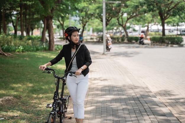 彼女の自転車で歩いて仕事の後ヘルメットを身に着けているアジアの若い女性