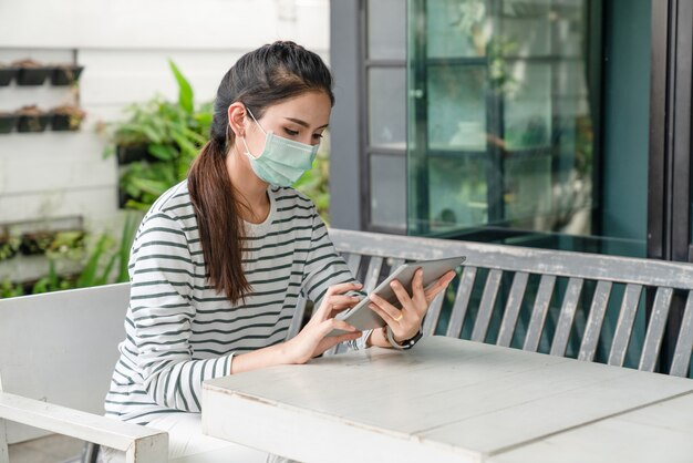 Asian young woman wearing medical mask to protect coronavirus or covid-19 disease while using tablet at the outside