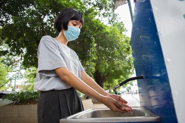 공공 장소에서 손을 씻는 의료 마스크를 쓴 아시아 젊은 여성
