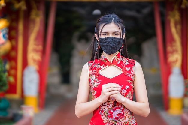 빨간색 중국 전통 치파오를 입고 신사에서 구정 축제를 위해 보호 마스크 세균을 착용 한 아시아 젊은 여성, covid-19 바이러스 확산 방지