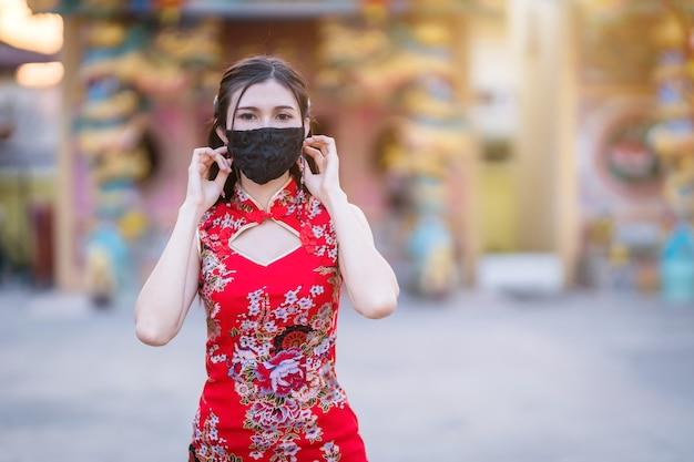 빨간색 중국 전통 치파오를 입고 아시아 젊은 여성이 보호 마스크를 착용
