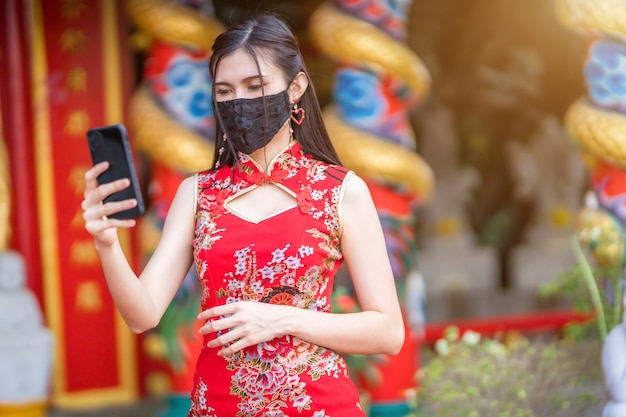 Asian young woman wearing red traditional chinese cheongsam, and wear protective mask and smartphone for chinese new year festival at shrine,prevention of the spread of covid-19 virus