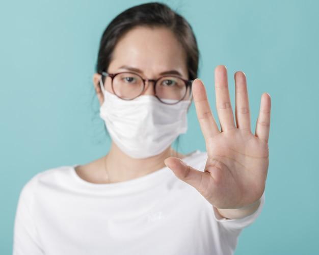 コロナウイルスの発生を防ぐためにマスクを着用し、アルコールゲルで手を洗うアジアの若い女性
