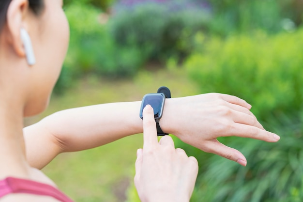 운동복을 착용하고 smartwatch를 운영하는 아시아 젊은 여자