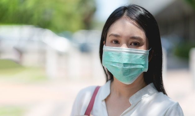 Asian young woman wearing surgical mask face protection