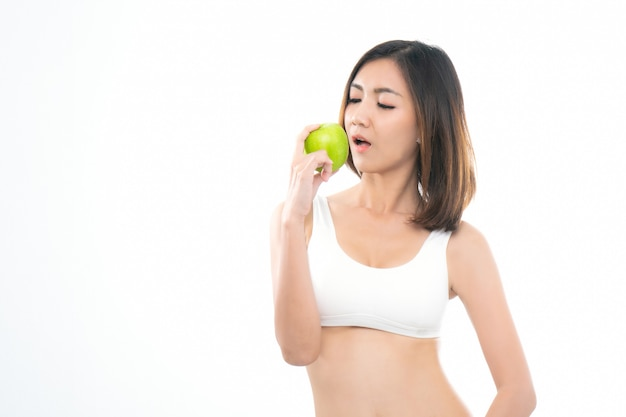 Asian young woman in white sport bra eating green apple.