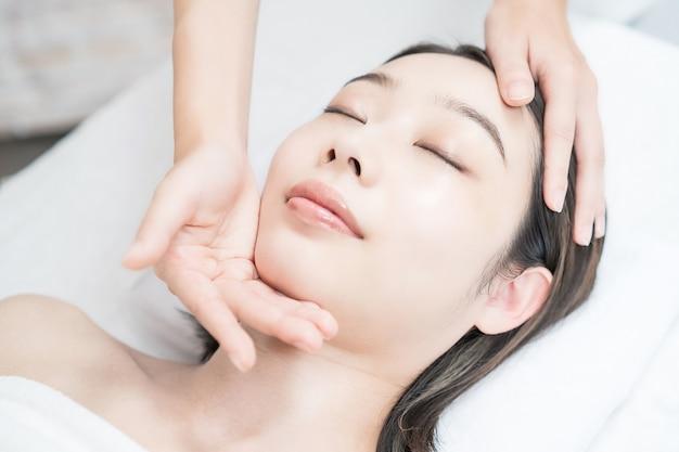 에스테틱 살롱에서 머리를 마사지 받는 아시아계 젊은 여성