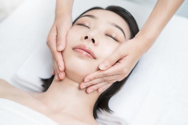 Азиатская молодая женщина, чья голова массируется в косметическом салоне