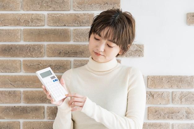 Азиатская молодая женщина с калькулятором и суровым взглядом