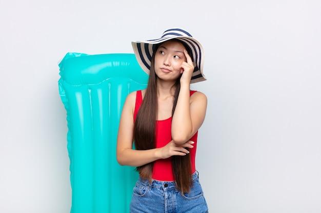 視線が集中したアジアの若い女性が、疑わしい表情で疑問に思い、上を向いて横を向いている。夏のコンセプト