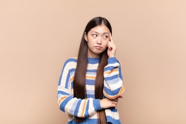 Азиатская молодая женщина с сосредоточенным взглядом, недоумевающая с сомнительным выражением лица, глядя вверх и в сторону
